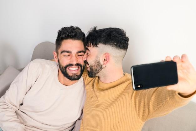 Pareja joven homosexual romántica tomando selfie en teléfono móvil