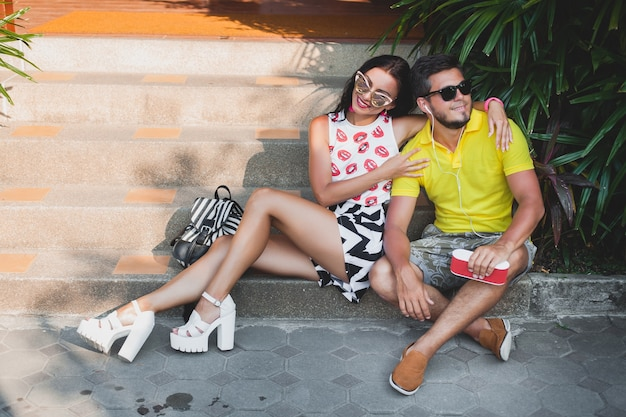 Pareja joven inconformista enamorada, escuchando música en el altavoz, sonriendo feliz, divirtiéndose, traje de verano, vacaciones tropicales, gafas de sol