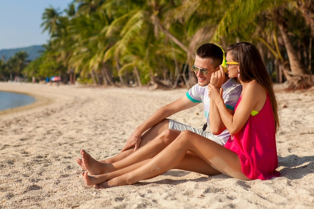 Pareja joven inconformista enamorada, playa tropical, vacaciones, estilo de moda de verano, gafas de sol, auriculares