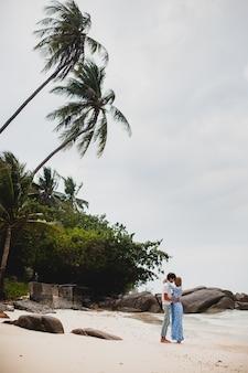 Pareja joven inconformista con estilo en el amor en la playa tropical durante las vacaciones