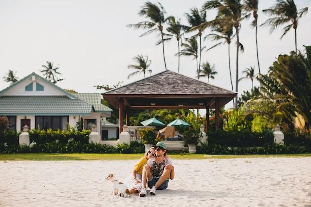Pareja joven inconformista con estilo enamorado caminando jugando perro cachorro jack russell, playa tropical, traje fresco, estado de ánimo romántico, divirtiéndose, soleado, hombre mujer juntos, horizontal, vacaciones, casa casa villa