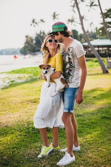 Pareja joven inconformista con estilo enamorado sosteniendo un perro en el parque tropical, sonriendo y divirtiéndose durante sus vacaciones
