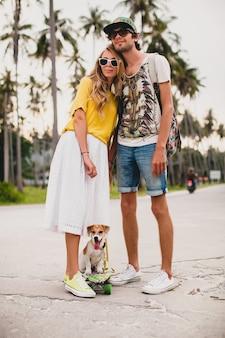 Pareja joven inconformista con estilo enamorado de vacaciones con perro y patineta, divirtiéndose