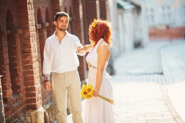 Pareja joven inconformista de moda en el amor caminando en las calles, clima soleado de primavera