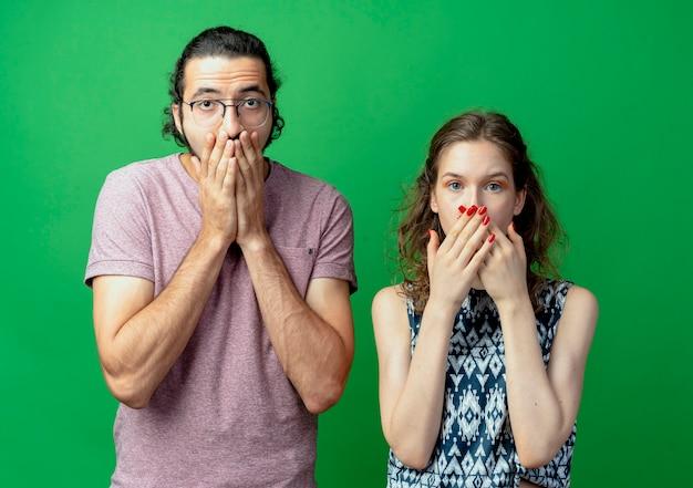 Pareja joven indignado, hombre y mujer, conmocionados y disgustados cubriendo la boca con las manos de pie sobre la pared verde