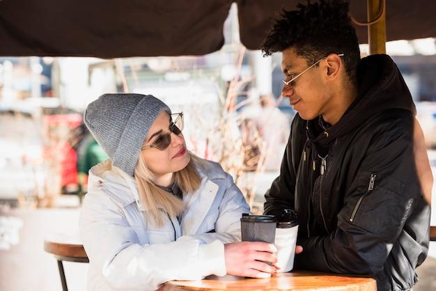 Pareja joven interracial joven rubia que sostiene la taza de café disponible que se sienta en caf�