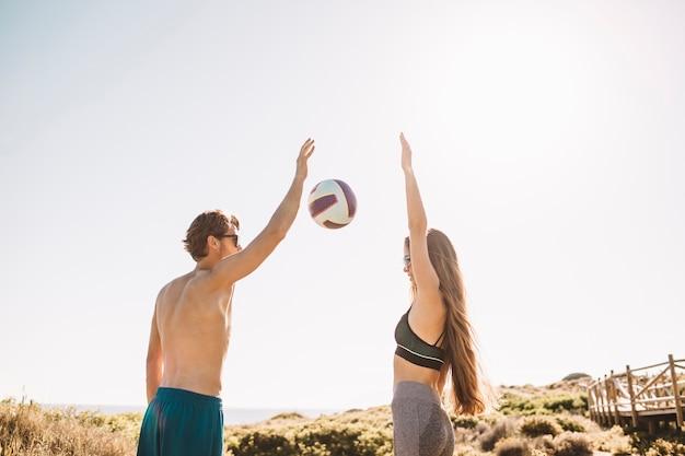 Pareja joven jugando al voleibol en la playa