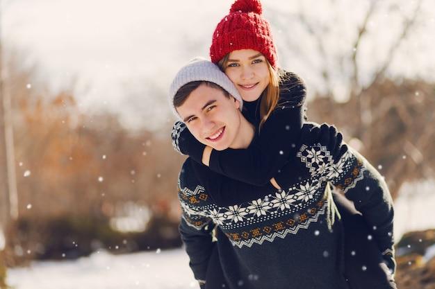Pareja joven jugando en un campo cubierto de nieve