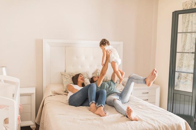Pareja joven jugando con la hija en la cama