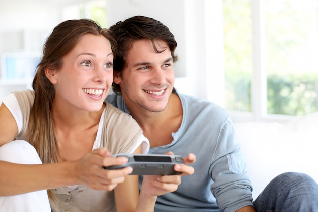 Pareja joven jugando videojuegos en casa