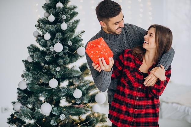 Pareja joven junto al árbol de navidad en casa