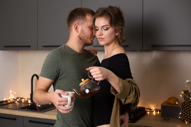 Pareja joven junto en la cocina con té, pasando un buen rato juntos.