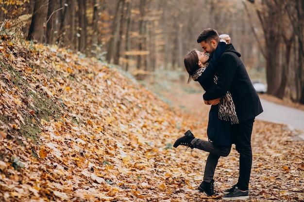 Pareja joven juntos caminando en un parque de otoño