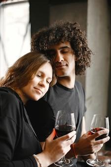 Pareja joven juntos sosteniendo copas de vino.