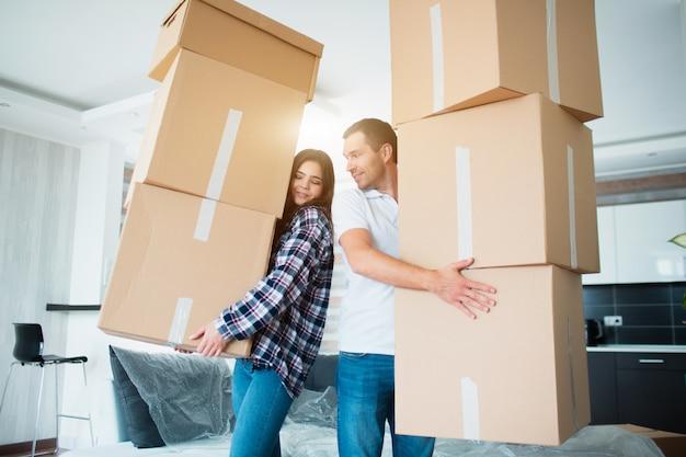 Pareja joven llevando muchas cajas de cartón una por una en el nuevo hogar. casa movil.