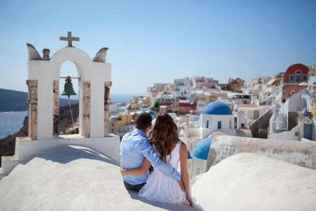 Pareja joven luna de miel en la isla más romántica de santorini, grecia