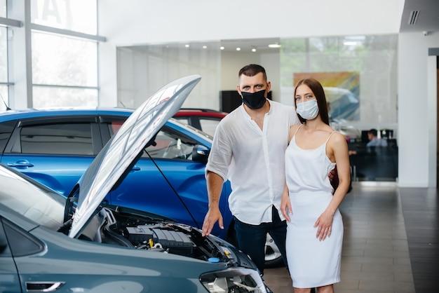 Pareja joven en máscaras selecciona un nuevo vehículo y consulta con un representante del concesionario en el período de la pandemia. venta de automóviles y vida durante la pandemia.