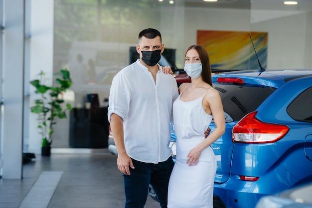 Pareja joven en máscaras selecciona un nuevo vehículo y consulta con un representante del concesionario en el período de la pandemia.
