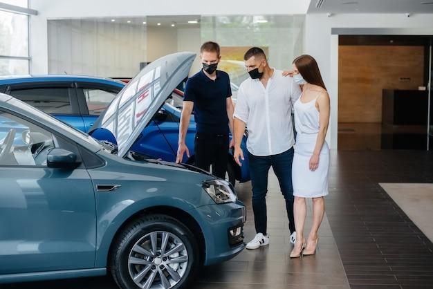 Una pareja joven con máscaras selecciona un vehículo nuevo y consulta con un representante del concesionario en el período de la pandemia. venta de automóviles y vida durante la pandemia.