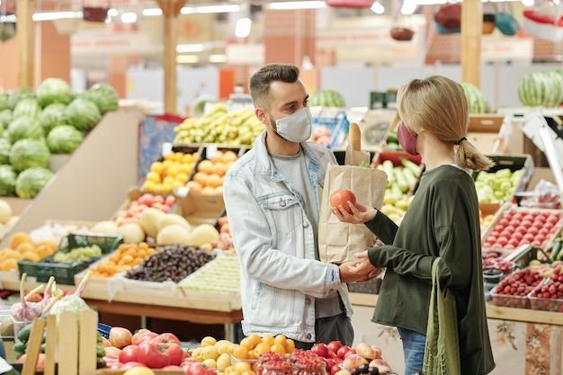 Pareja joven en máscaras de tela de pie en el mostrador y comprar alimentos orgánicos en el mercado: chica eligiendo tomates