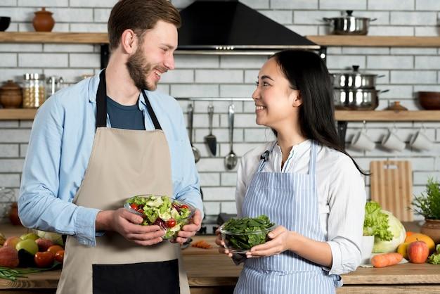 Pareja joven mirando el uno al otro mientras sostiene un tazón de ensalada y hojas verdes frescas