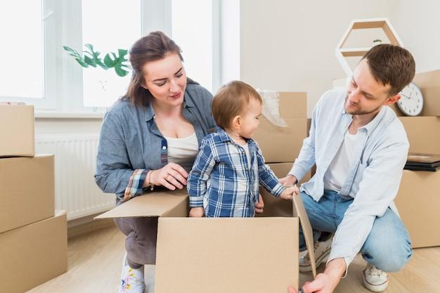 Pareja joven mirando a su hijo pequeño de pie dentro de la caja de cartón en la sala de estar