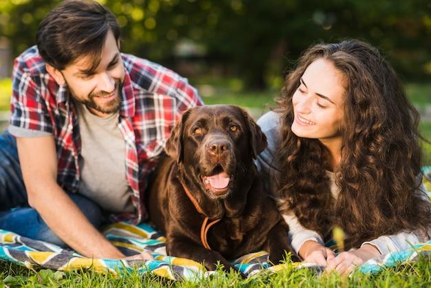 Pareja joven mirando a su perro lindo en el parque