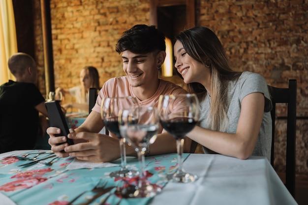Pareja joven mirando un teléfono inteligente en un restaurante.