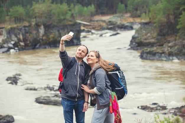 Pareja joven en las montañas con mochilas en la primavera hace un selfie