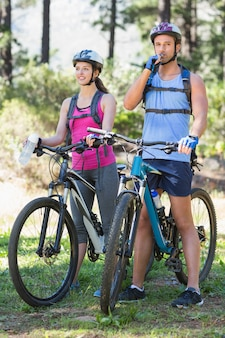 Pareja joven montando bicicleta en el bosque