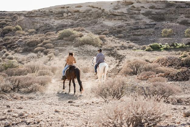 Pareja joven montando a caballo haciendo excursión al atardecer - el foco principal en la espalda de la mujer