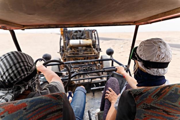 Pareja joven montando coche buggy en el desierto