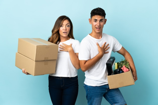 Pareja joven moviéndose en casa nueva entre cajas en azul sorprendido y conmocionado mientras mira a la derecha