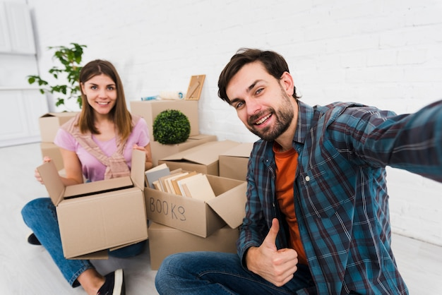 Pareja joven moviéndose juntos en casa nueva; desempaquetar cajas de cartón; tomando sulfuro
