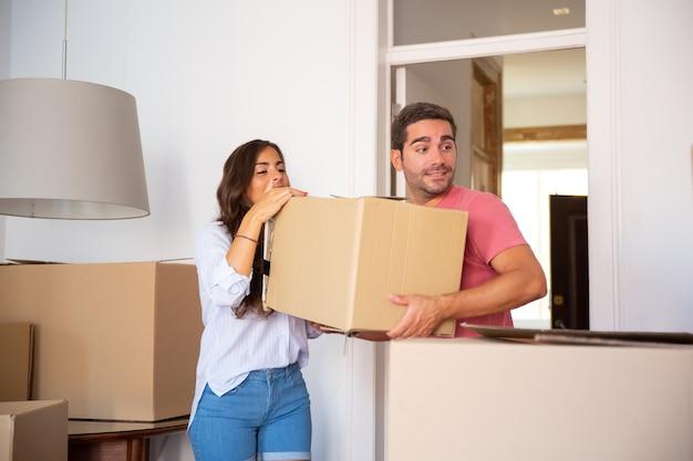 Pareja joven mudándose a casa nueva, llevando cajas de cartón