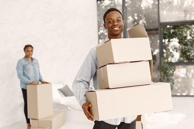 Pareja joven mudándose juntos al nuevo hogar. pareja afroamericana con cajas de cartón.
