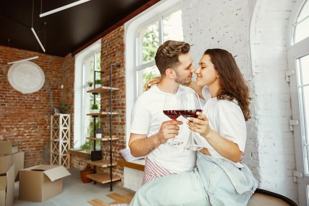 Pareja joven se mudó a una nueva casa o apartamento. beber vino tinto, acariciar y relajarse después de limpiar y desempacar. luce feliz y confiado. familia, mudanza, relaciones, primer concepto de hogar.