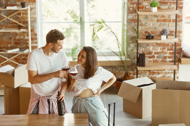 Pareja joven se mudó a una nueva casa o apartamento. beber vino tinto, sonreír y relajarse después de limpiar y desempacar. luce feliz y confiado. familia, mudanza, relaciones, primer concepto de hogar.