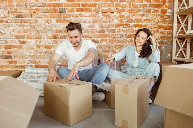 Pareja joven se mudó a una nueva casa o apartamento. desempacando cajas de cartón juntas, divirtiéndose en el día de la mudanza. luce feliz, soñadora y confiada. familia, mudanza, relaciones, primer concepto de hogar.