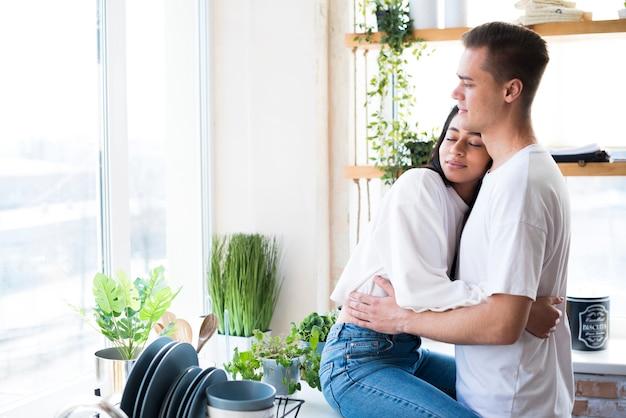 Pareja joven multiétnica en el amor que abraza en cocina