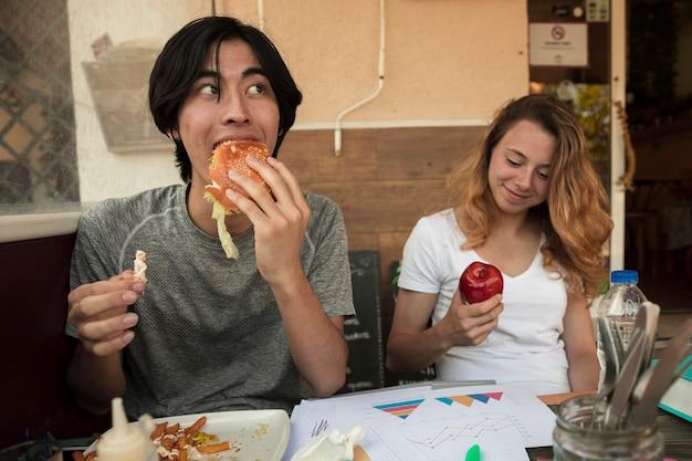 Pareja joven multirracial comiendo comida rápida cerca de la mesa con diagramas