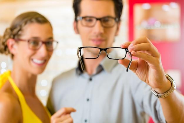 Pareja joven en óptica con gafas