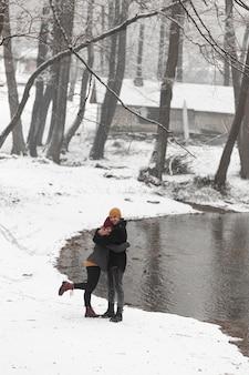 Pareja joven en paisaje de invierno con árboles y lago