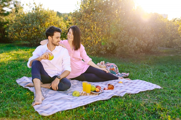 Pareja joven en el parque al aire libre haciendo un picnic
