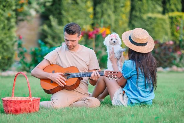 Pareja joven en el parque tocando la guitarra