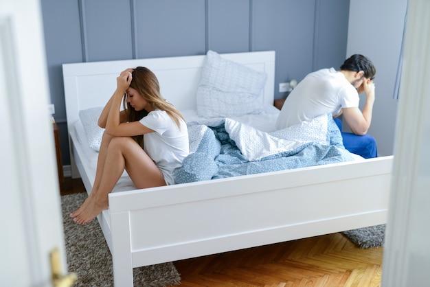 Pareja joven peleando en su dormitorio. ambos sentados al otro lado de la cama luciendo tristes y decepcionados.