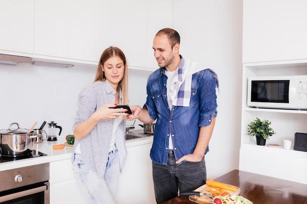 Pareja joven de pie en la cocina usando el teléfono móvil mientras se cocina la comida