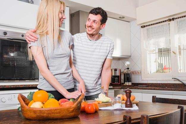 Pareja joven de pie detrás de la mesa de madera cortar verduras en la cocina
