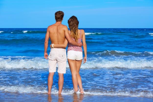 Pareja joven de pie mirando a la playa trasera