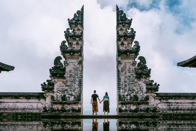 Pareja joven de pie en las puertas del templo y tomados de la mano en el templo lempuyang luhur en bali, indonesia. tono de la vendimia